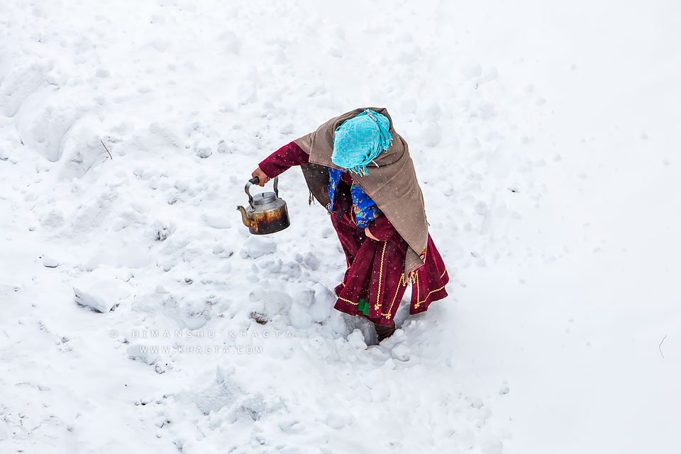 A lady carrying a tea pot walks through snow in Kaza village of Spiti